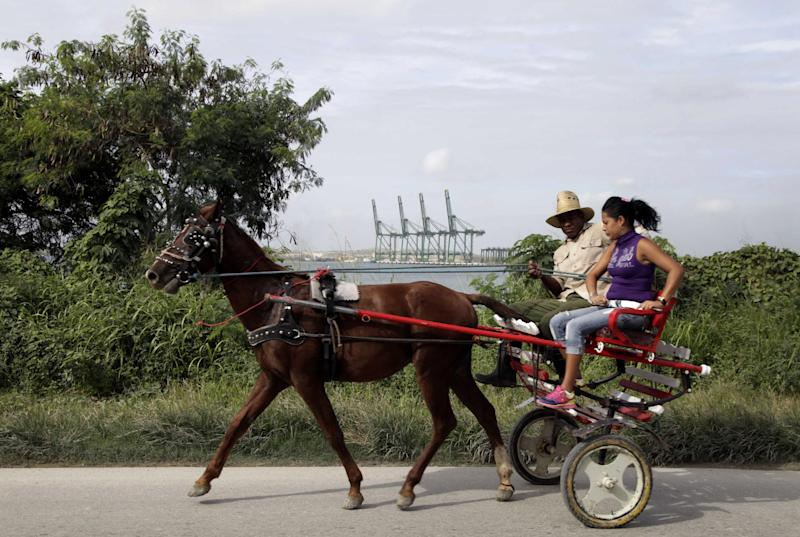 In this Nov. 6, 2013 photo, a man drives his horse drawn carriage past a port under construction in Mariel Bay in Mariel, Cuba. For the residents of Mariel, the new port means new jobs, a window into the global economy and perhaps a few more cars on the streets. (AP Photo/Franklin Reyes)