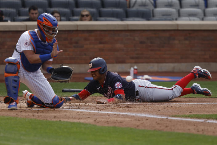 Washington Nationals' Starlin Castro, tight, beats the throw to New York Mets' James McCann, left, and scores on a single by Joe Ross during the second inning of a baseball game, Saturday, April 24, 2021, in New York. (AP Photo/Jason DeCrow)