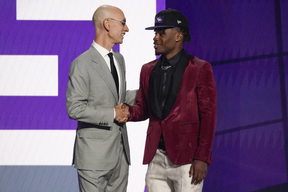 Davion Mitchell, right, is greeted by NBA Commissioner Adam Silver after being selected ninth overall by the Sacramento Kings during the NBA basketball draft, Thursday, July 29, 2021, in New York. (AP Photo/Corey Sipkin)