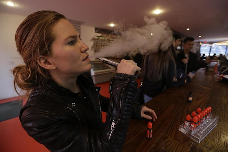 In this Feb. 20, 2014 photo, Talia Eisenberg, co-founder of the Henley Vaporium, uses her vaping device in New York. The vaporium is an intimate hipster hangout in the Soho neighborhood with overstuffed chairs, exposed brick, friendly counter help, but no booze. Instead, the proprietors are peddling e-cigarettes, along with bottles of liquid nicotine ready to be plucked from behind a wooden bar and turned into flavorful vapor for a lung hit with a kick that is intended to simulate traditional smoking. (AP Photo/Frank Franklin II)