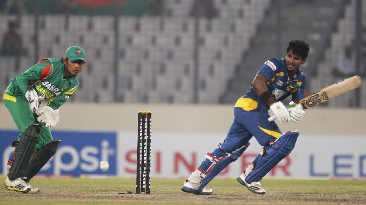 Sri Lanka's Kusal Perera plays a shot as Bangladesh's wicketkeeper Anamul Haque (L) watches during their third one day international (ODI) cricket match of the series in Dhaka February 22, 2014. REUTERS/Andrew Biraj (BANGLADESH - Tags: SPORT CRICKET)