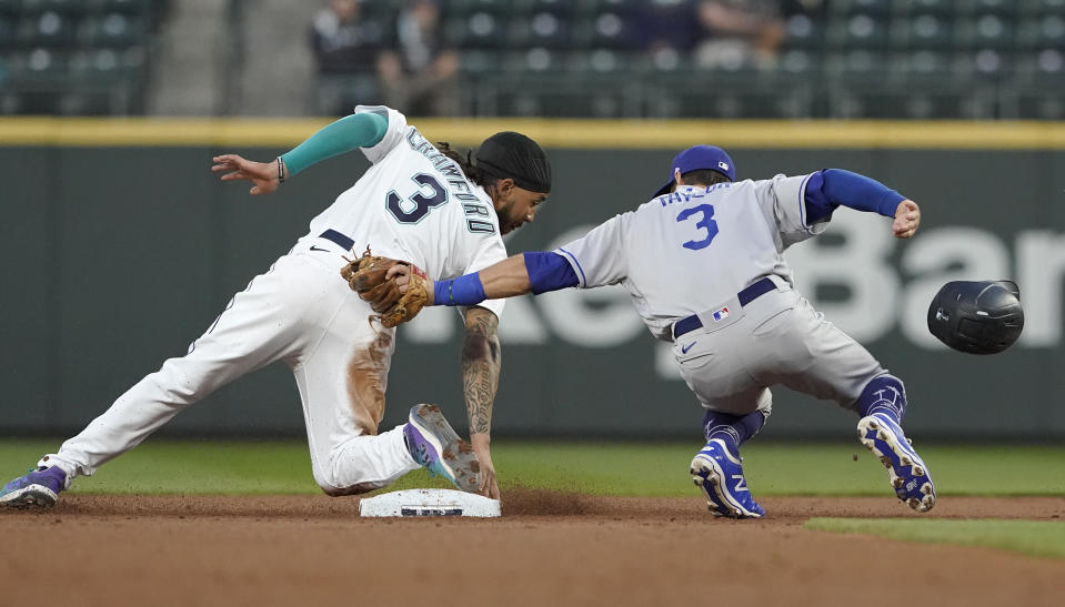 Los Angeles Dodgers second baseman Chris Taylor, right, tries to put a tag on Seattle Mariners' J.P. Crawford, left, as Crawford attempts to steal second during the second inning of a baseball game, Monday, April 19, 2021, in Seattle. Crawford was called out on the play. (AP Photo/Ted S. Warren)