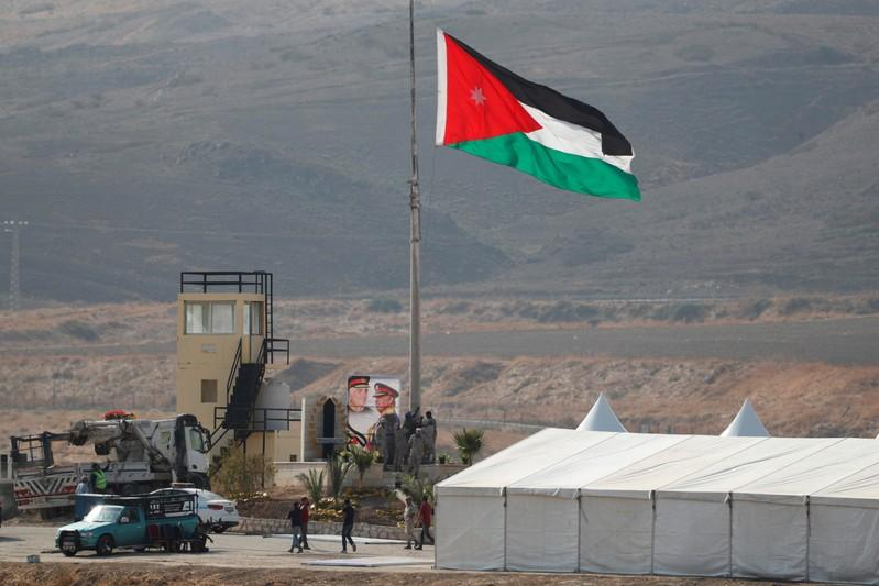 """A Jordanian national flag is lifted near a tent at the """"Island of Peace"""" in an area known as Naharayim in Hebrew and Baquora in Arabic, on the Jordanian side of the border with Israel, as seen from the Israeli side"""
