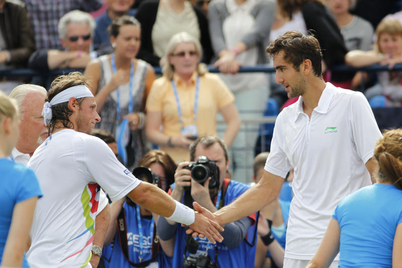 Argentina's David Nalbandian, left, shakes hand with Croatia's Marin Cilic after Nalbandian was disqualified for causing an injury to the line judge during the Queen's Club grass court championships final tennis match, London, Sunday, June 17, 2012. (AP Photo/Sang Tan)