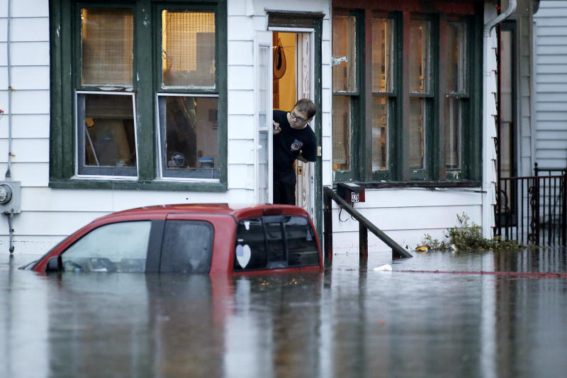 A man in a home along High St. waits for rescuers to come back for him after overnight thunderstorms flooded much of Westville, N.J. on Thursday, June 20, 2019. (Elizabeth Robertson/The Philadelphia Inquirer via AP)