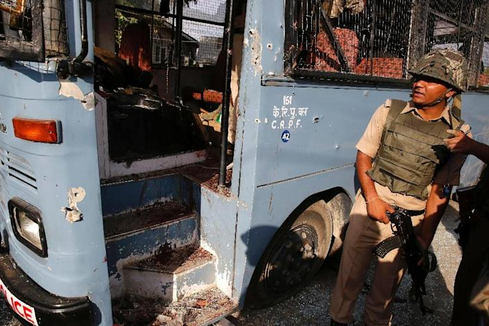 An Indian security officer stands next to a bus that had been carrying paramilitary troopers when it was attacked by suspected militants in Pampore, south of Srinagar, on June 25, 2016 (AFP Photo/)