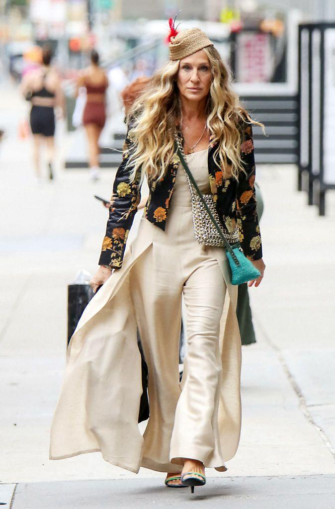 """<p>Never missing a trick with style, Carrie Bradshaw would naturally know the best vintage shops to source statement pieces from, such as this cream Claude Montana linen jumpsuit from<a href=""""https://www.instagram.com/p/CRRm9Axtpe8/"""" rel=""""nofollow noopener"""" target=""""_blank"""" data-ylk=""""slk:Replika Vintage,"""" class=""""link rapid-noclick-resp""""> Replika Vintage,</a> NYC. </p><p>Over the jumpsuit, Parker wore a silk floral blazer by Dries Van Noten.</p><p> <a class=""""link rapid-noclick-resp"""" href=""""https://www.net-a-porter.com/en-gb/shop/product/dries-van-noten/quilted-floral-print-velvet-jacket/1274029"""" rel=""""nofollow noopener"""" target=""""_blank"""" data-ylk=""""slk:SHOP SIMILAR"""">SHOP SIMILAR</a> Dries Van Noten Quilted floral-print velvet jacket, £519 </p>"""
