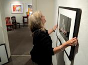 This July 27, 2013 image shows Thea Swengel of the David Anthony Fine Art gallery in Taos, N.M., hanging a portrait of George Harrison that was taken in 1964 by photographer Mike Mitchell during the Beatles' first live concern on American soil. Mitchell's portraits of the Beatles are the centerpiece of a monthlong photography exhibition at the gallery. This marks the first time the portraits have been exhibited since their 2011 unveiling at a Christie's auction in New York City. (AP Photo/Susan Montoya Bryan)