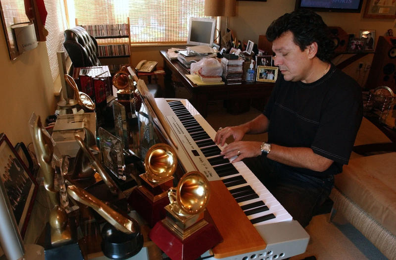 """FILE - This Jan. 6, 2005 file photo shows Latin songwriter Rudy Perez working on a composition at his home in Miami Beach, Fla. Perez has written a memoir titled """"The Latin Hitmaker: My Journey from Cuban Refugee to World-Renowned Record Producer and Songwriter."""" (AP Photo/J. Pat Carter, File)"""