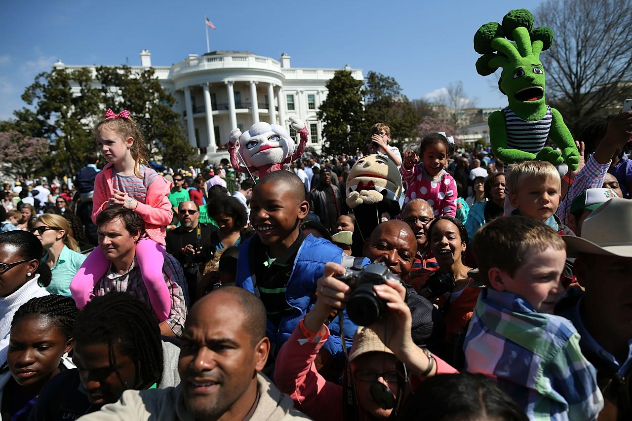 WASHINGTON, DC - APRIL 01: People watch as U.S. President Barack Obama reads a book to children during the annual Easter Egg Roll on the White House tennis court April 1, 2013 in Washington, DC. Thousands of people are expected to attend the 134-year-old tradition of rolling colored eggs down the White House lawn that was started by President Rutherford B. Hayes in 1878.  (Photo by Mark Wilson/Getty Images)