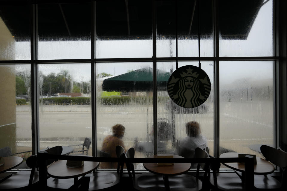 Krystina Francois, left, and Francesca Menes, children of Haitian immigrants to the U.S. and co-founders of the Black Collective, are seen through windows streaked from a recent rain, as they work together outside a Starbucks, Tuesday, Sept. 21, 2021, in Miami Shores, Fla. Menes and Francois, whose advocacy organization focuses on the political needs and economic empowerment of Black people across the African diaspora, have called for the Biden administration to immediately suspend plans to remove migrants via planes bound for Haiti. (AP Photo/Rebecca Blackwell)