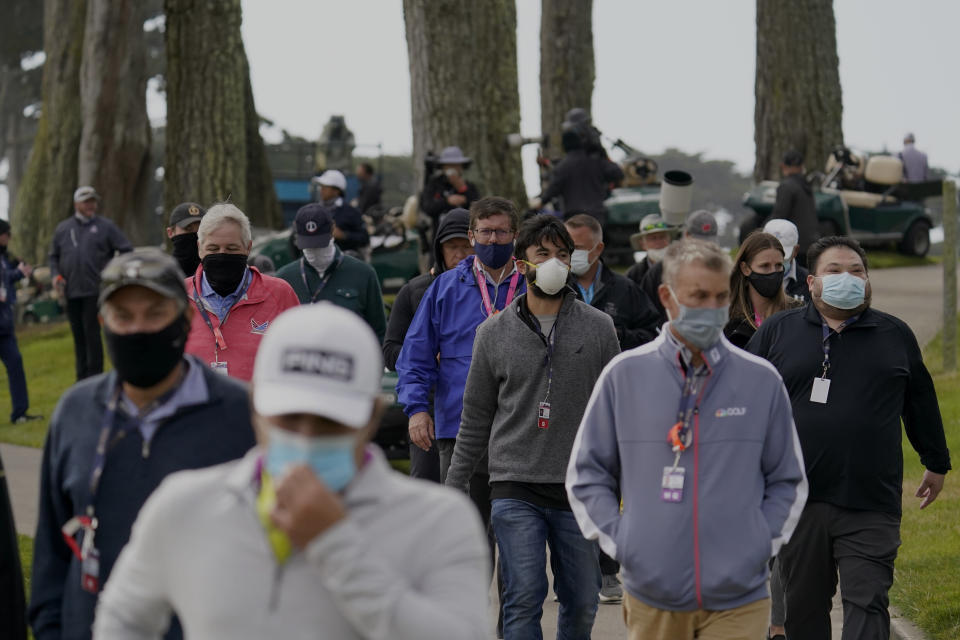 Members of the gallery wearing face mass follow the Tiger Woods group on the 13th hole during the first round of the PGA Championship golf tournament at TPC Harding Park Thursday, Aug. 6, 2020, in San Francisco. (AP Photo/Jeff Chiu)