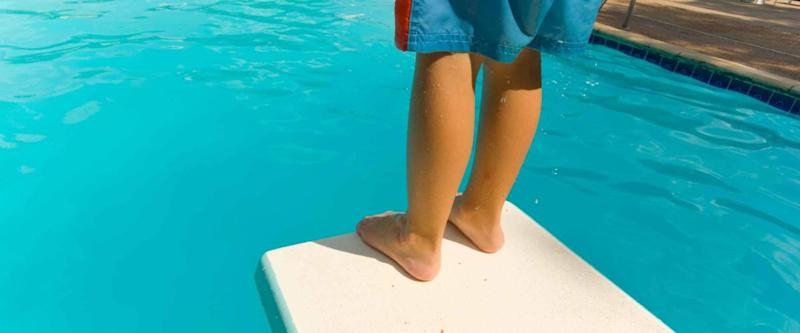 Young boy standing on the end of a diving board at a swimming pool - seems to be a little apprehension