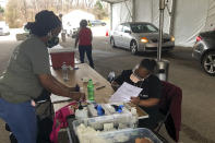 Workers organize paperwork and medical supplies as people wait in their cars to get a COVID-19 vaccination on Friday, March 12, 2021, in Memphis, Tenn. As millions continue to wait their turn for the COVID-19 vaccine, small but steady amounts of the precious doses have gone to waste across the country. It's a heartbreaking reality that experts acknowledged was always likely to occur. (AP Photo/Adrian Sainz)