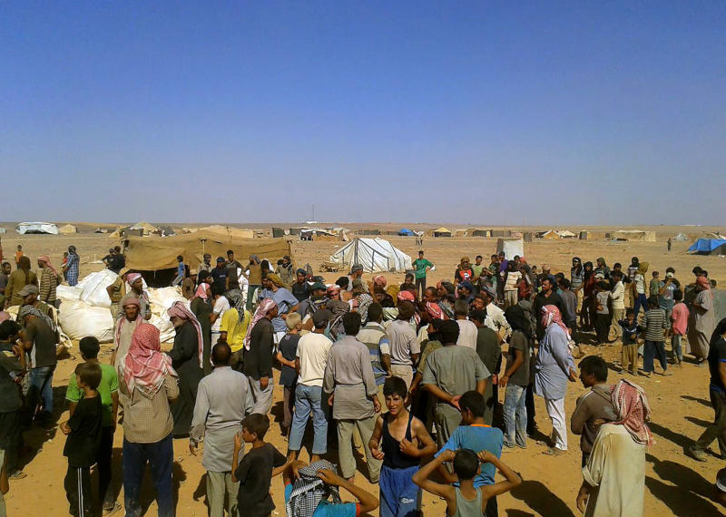 FILE - In this Aug. 4, 2016 file photo, displaced people wait to receive aid at the Rukban camp, near the Jordan-Syria border. The U.S. military said Monday, April, 8, 2019 that it is not preventing Syrians from leaving the remote Rukban camp near an American base in Syria and is urging Russia and Damascus to help facilitate the delivery of humanitarian aid. Russia has recently called for the camp to be dismantled and accused the U.S. of hindering such efforts. (AP Photo, File)