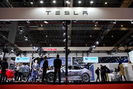 FILE PHOTO: People visit a Tesla booth during the media day for the Shanghai auto show in Shanghai, China April 16, 2019. REUTERS/Aly Song/File Photo