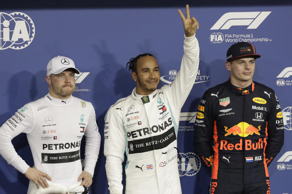 Mercedes driver Lewis Hamilton of Britain, centre, celebrates his pole position with Mercedes driver Valtteri Bottas of Finland, left, and Red Bull driver Max Verstappen of the Netherland's during the qualifying session at the Yas Marina racetrack in Abu Dhabi, United Arab Emirates, Saturday, Nov. 30, 2019. The Emirates Formula One Grand Prix will take place on Sunday. (AP Photo/Luca Bruno)