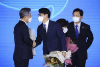 Gyeonggi Gov. Lee Jae-myung, left, one of the ruling Democratic Party's contenders for next year's presidential election, shakes hands with another candidate Park Yong-jin after winning the final race to run for the president in Seoul, South Korea, Sunday, Oct. 10, 2021. (Kim Hong-ji/Pool Photo via AP)