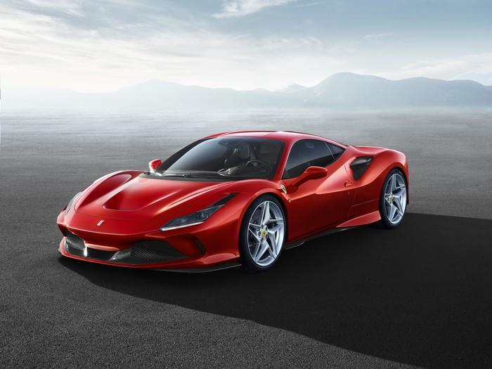 A red Ferrari F8 Tributo, with mountains in the background