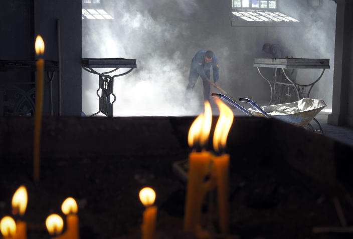 Church workers sweep the dust in the Holy Savior Cathedral, damaged by shelling by Azerbaijan's artillery during a military conflict in Shushi, the separatist region of Nagorno-Karabakh, Saturday, Oct. 24, 2020. The heavy shelling forced residents of Stepanakert, the regional capital of Nagorno-Karabakh, into shelters, as emergency teams rushed to extinguish fires. Nagorno-Karabakh authorities said other towns in the region were also targeted by Azerbaijani artillery fire. (AP Photo)