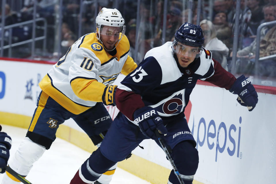 Nashville Predators center Colton Sissons, back, and Colorado Avalanche left wing Matt Nieto pursue the puck along the boards during the first period of an NHL hockey game Thursday, Nov. 7, 2019, in Denver. (AP Photo/David Zalubowski)