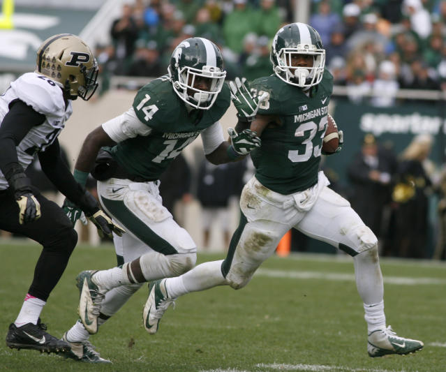 Michigan State's Jeremy Langford, right, rushes against Purdue's Antoine Lewis, left, as Michigan State's Tony Lippett (14) blocks during the fourth quarter of an NCAA college football game, Saturday, Oct. 19, 2013, in East Lansing, Mich. Langford had 131 yards rushing in Michigan State's 14-0 win. (AP Photo/Al Goldis)