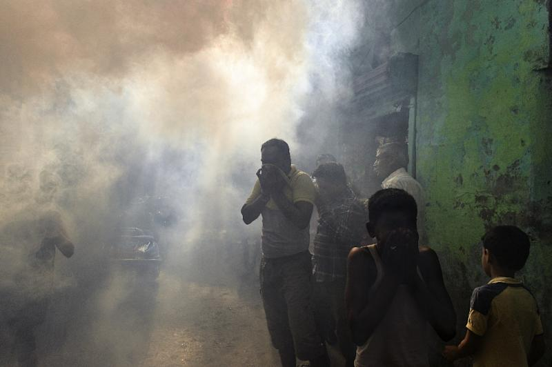 Indian residents come out of their homes as a municipal worker fumigates the area to kill disease-spreading mosquitoes in New Delhi on September 3, 2015