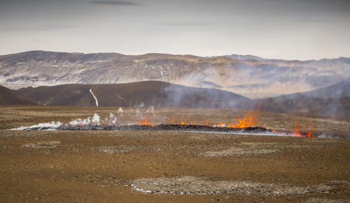 Steam and lava spurt from a new fissure on a volcano on the Reykjanes Peninsula in southwestern Iceland, Monday, April 5, 2021. The new fissure has opened up at the Icelandic volcano that began erupting last month, prompting the evacuation of hundreds of hikers who had come to see the spectacle. Officials say the new fissure is about 500 meters (550 yards) long and about one kilometer (around a half-mile) from the original eruption site in the Geldinga Valley (AP Photo/Marco Di Marco)