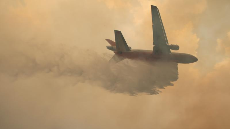 A plane drops water over wildfires burning in the vicinity of Tapitallee, New South Wales, Australia on 4 January 2020. High winds and temperatures over 100 degrees Fahrenheit were likely to exacerbate fires already raging out of control on Saturday; Officials in New South Wales said they expected to lose more houses over the weekend. Image: Matthew Abbott/NYT