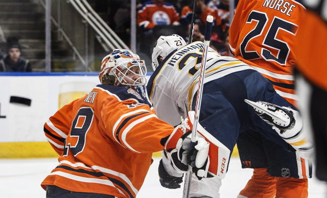 Buffalo Sabres' Sam Reinhart (23) tries to screen Edmonton Oilers goalie Mikko Koskinen (19) during first period NHL hockey action in Edmonton, Alberta, on Monday, Jan. 14, 2019. (Jason Franson/The Canadian Press via AP)