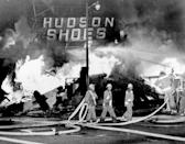 FILE - In this Aug. 14, 1965, file photo, firefighters battle a blaze set in a shoe store that collapses in flames in the Los Angeles community of Watts. Watts has been associated with an uprising in 1965 that led to burned-down buildings and bloodshed. But when some protests against racial injustice in 2020 devolved into vandalism and looting, Watts has been peaceful. (AP Photo/File)