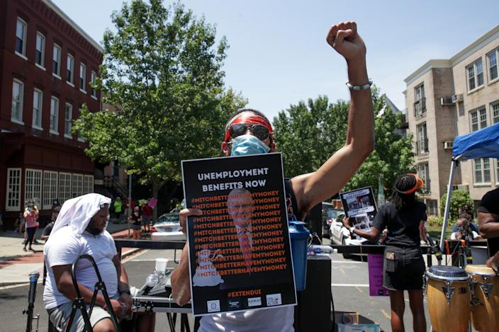 A person holds a placard and raises a fist as protesters temporarily block the street to U.S. Senate Majority Leader Mitch McConnell's (R-KY) house with a live band on a flatbed truck, demanding the extension of coronavirus disease (COVID-19)-related unemployment aid, on Capitol Hill in Washington, U.S. July 22, 2020. (Jonathan Ernst/Reuters)