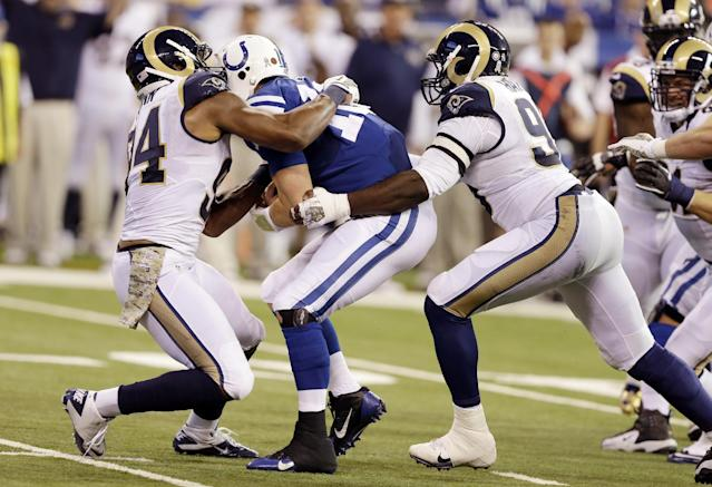 Indianapolis Colts quarterback Andrew Luck, center, is sacked by St. Louis Rams defensive ends Robert Quinn, left, and William Hayes during the first half of an NFL football game in Indianapolis, Sunday, Nov. 10, 2013. (AP Photo/Darron Cummings)