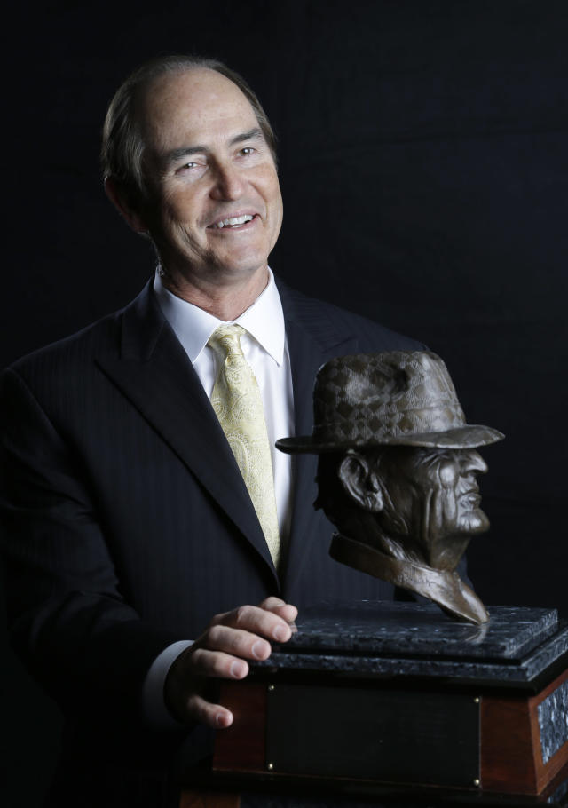 """Baylor football coach Art Briles, a finalist for the Paul """"Bear"""" Bryant college coach of the year award, poses with the trophy Wednesday, Jan. 15, 2014, in Houston. (AP Photo/Pat Sullivan)"""