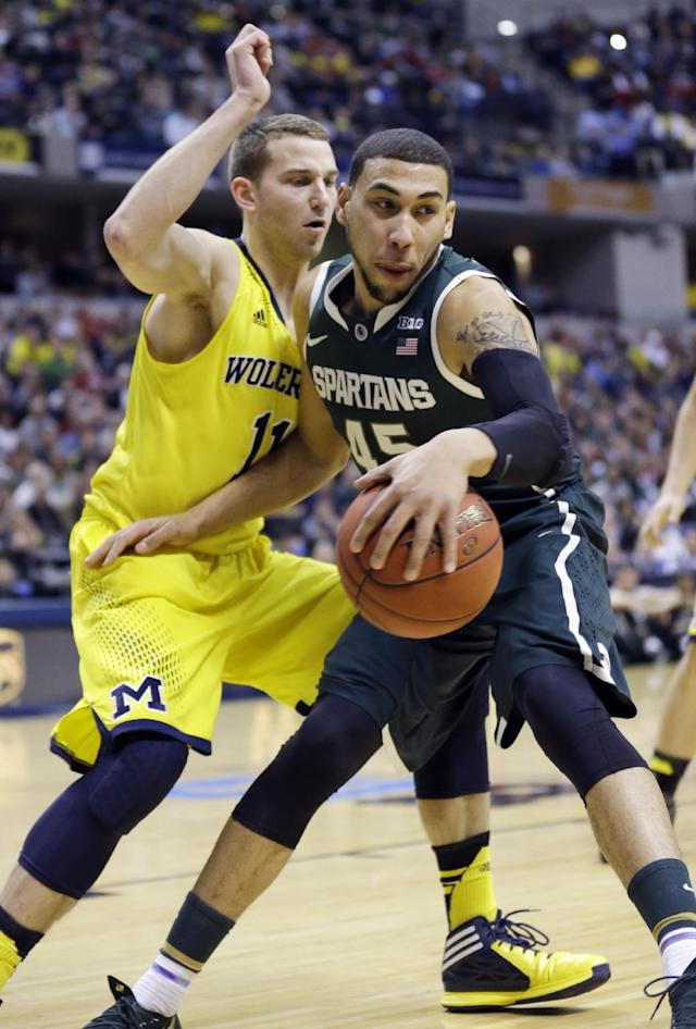 Michigan State guard Denzel Valentine (45) drives the ball against Michigan guard Nik Stauskas (11) in the first half of an NCAA college basketball game in the championship of the Big Ten Conference tournament Sunday, March 16, 2014, in Indianapolis. (AP Photo/Michael Conroy)