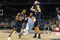 Minnesota Timberwolves' Josh Okogie, center, makes his way between Orlando Magic's Wes Iwundu, left, and Nikola Vucevic in the first half of an NBA basketball game, Friday, March 6, 2020, in Minneapolis. (AP Photo/Jim Mone)
