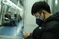 A man wearing two face masks travels in the subway, as the country is hit by an outbreak of the new coronavirus, in Beijing