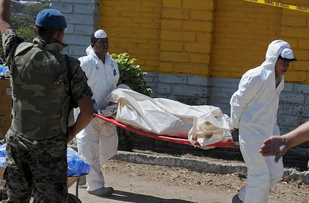 Forensic workers carry away the body of an inmate who died in a prison fire in Comayagua, Honduras, 90 miles (140 kilometers) north of the capital, Tegucigalpa, Honduras, Wednesday Feb. 15, 2012. At least 300 inmates were killed and 21 are injured, according to authorities. (AP Photo/Fernando Antonio)