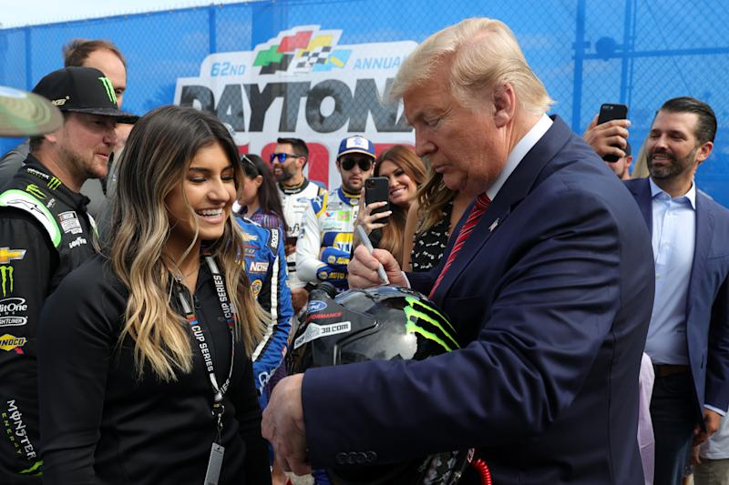 DAYTONA BEACH, FLORIDA - FEBRUARY 16: U.S. President Donald Trump speaks signs the helmet of Hailie Deegan prior to the NASCAR Cup Series 62nd Annual Daytona 500 at Daytona International Speedway on February 16, 2020 in Daytona Beach, Florida. (Photo by Chris Graythen/Getty Images)