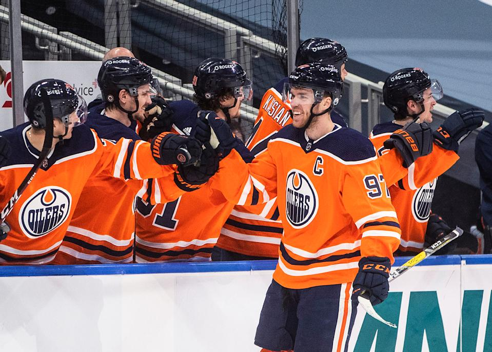 Edmonton Oilers' Connor McDavid (97) is congratulated for his goal against the Calgary Flames during the third period of an NHL hockey game Friday, April 2, 2021, in Edmonton, Alberta. (Jason Franson/The Canadian Press via AP)