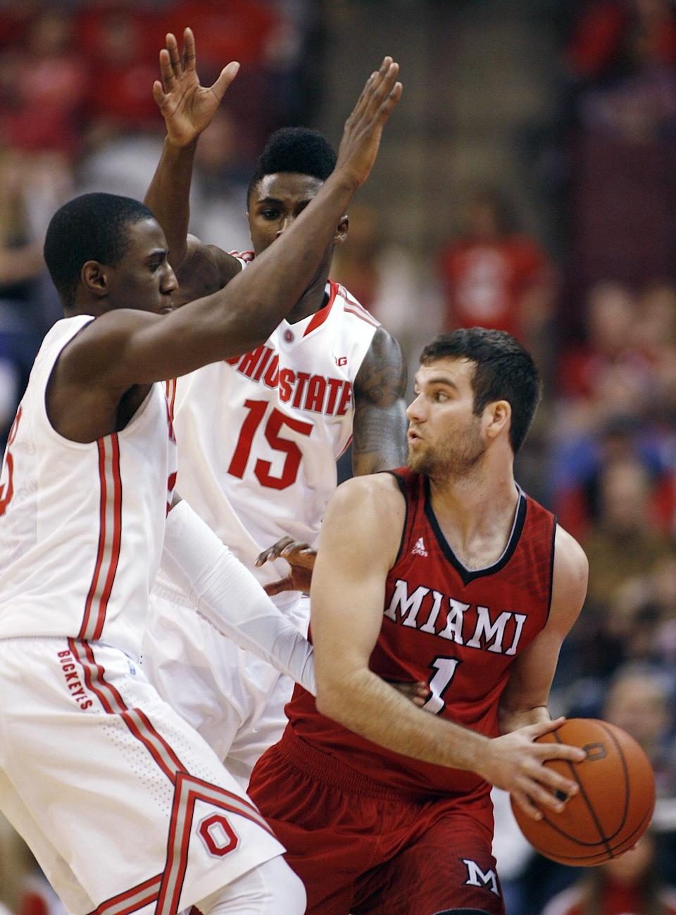 Ohio State's Shannon Scott and Kam Williams (15) pressure Miami's Zack McCormick during the second half of an NCAA college basketball game, Monday, Dec. 22, 2014, in Columbus, Ohio. Ohio State won 93-55. (AP Photo/Mike Munden)