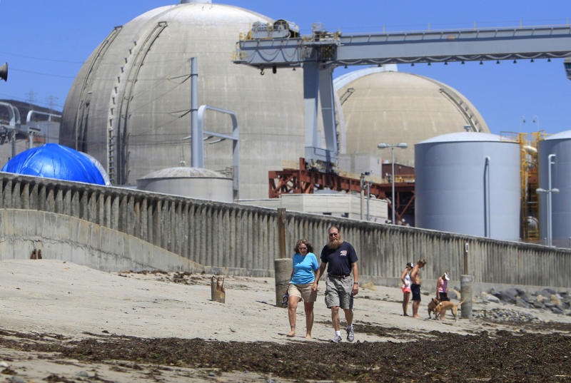 FILE - This file photo taken June 30, 2011 shows beach-goers walking on the sand near the San Onofre nuclear power plant in San Clemente , Calif. The twin reactors at the plant have been idled while investigators determine why tubing carrying radioactive water is eroding at an unusual rate, and the Nuclear Regulatory Commission chairman will visit the plant Friday, April 6, 2012, to highlight the agency's concern over the ailing equipment. (AP Photo, Lenny Ignelzi, File)