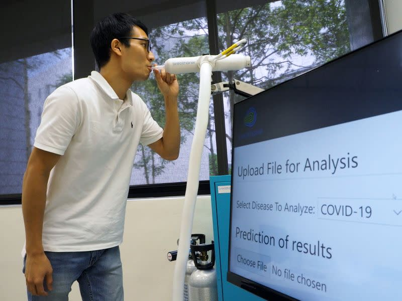 A staff member demonstrates the usage of Breathonix breathalyzer test kit in Singapore
