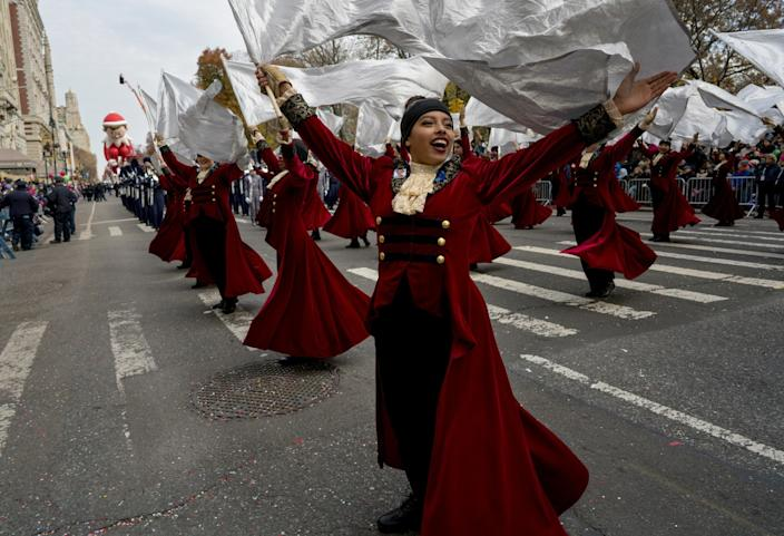 High school band members, in costumes of swirling robes and lace jabots, carry streaming white flags.