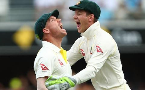 David Warner of Australia celebrates with team mate Tim Paine after taking a catch to dismiss Jake Ball of England during day two of the First Test Match of the 2017/18 Ashes Series between Australia and England at The Gabba - Credit: Chris Hyde - CA/Cricket Australia/Getty Images