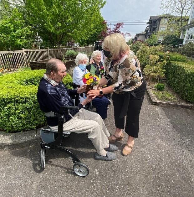 Treena Innes, right, founder of Bouquets for Baba, hands a surprise gift of flowers to isolated seniors in Maple Ridge, B.C. She launched the initiative to let seniors know they are cared for. (Greg Rasmussen/CBC - image credit)