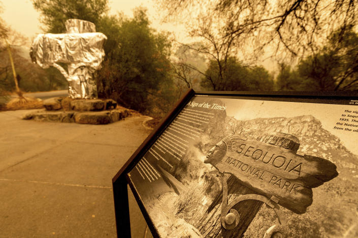 FILE - In this Wednesday, Sept. 15, 2021, file photo, fire-resistant wrap covers an historic welcome sign as the KNP Complex Fire burns in Sequoia National Park, Calif. More than 2,000 firefighters are on the lines Monday, Sept. 27, as the 133-square-mile Windy Fire burns on the Tule River Indian Reservation and in Sequoia National Forest. (AP Photo/Noah Berger, File)