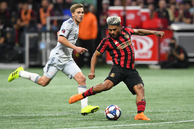 Atlanta United forward Josef Martinez (7) kicks a shot on goal as New England Revolution midfielder Scott Caldwell follows during round one of an MLS Cup playoff soccer game Saturday, Oct. 19, 2019, in Atlanta. Atlanta United won 1-0. (AP Photo/John Amis)