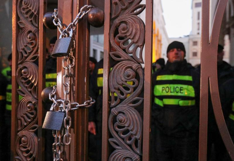 Opposition supporters chain the gate of the parliament during a rally to protest against the government and demand an early parliamentary election, in Tbilisi