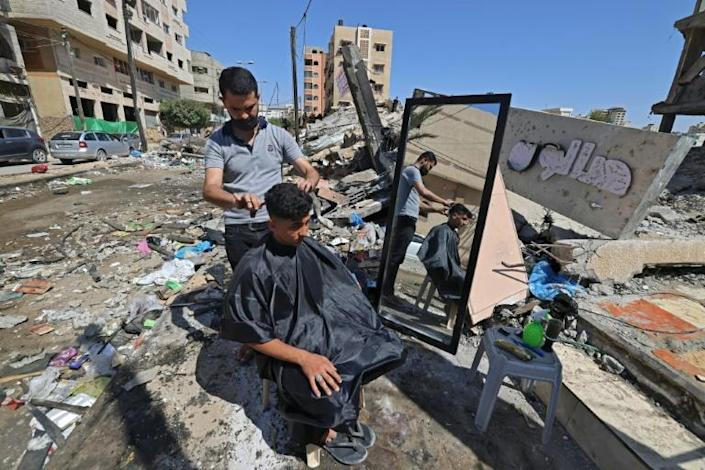 A Palestinian barber works next to the ruins of buildings and shops destroyed by Israeli strikes in Gaza
